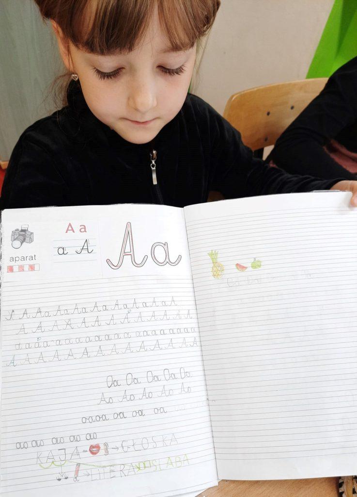 Fotografia przedstawia ucznia klasy pierwszej trzymającą swój otwarty zeszyt.
