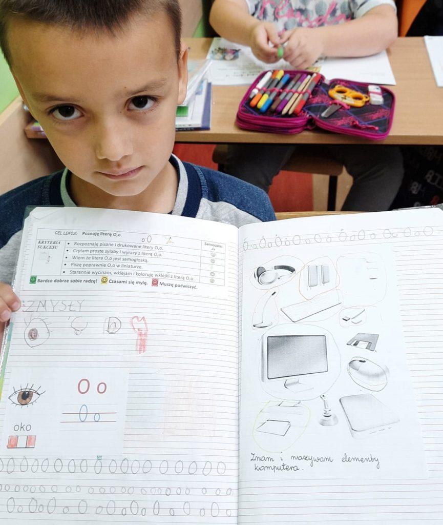 Fotografia przedstawia ucznia klasy pierwszej trzymającego swój otwarty zeszyt.