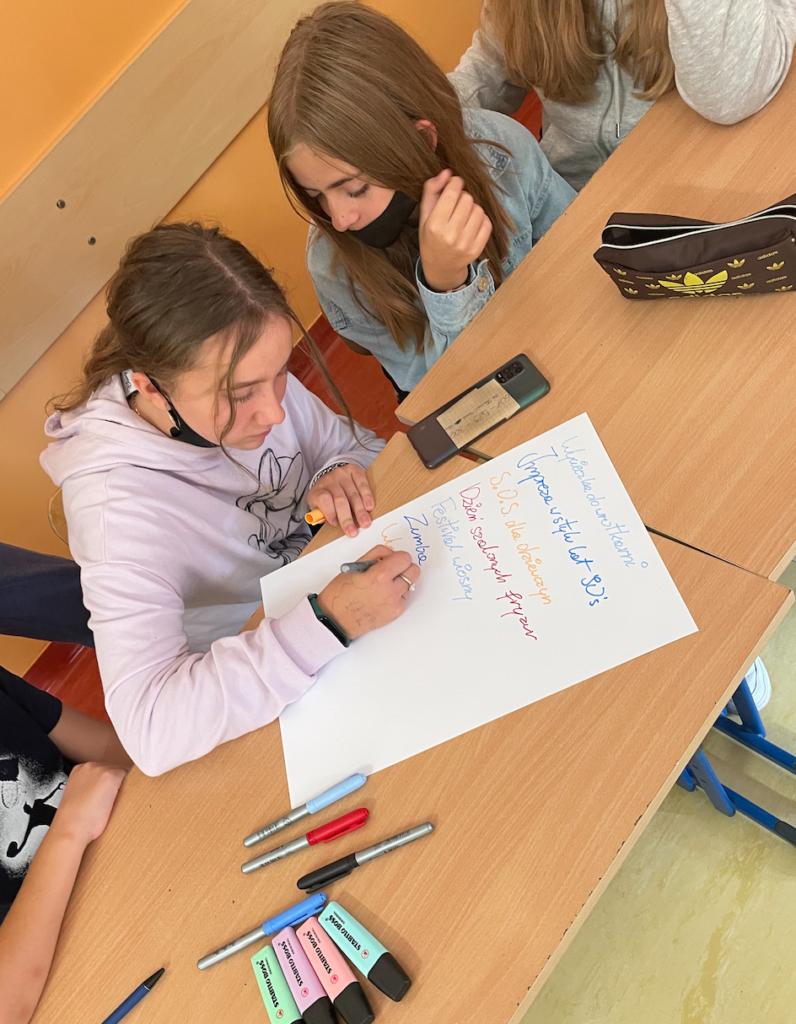 Dwie uczennice piszące propozycje działań dla uczniów w nowym roku szkolnym
