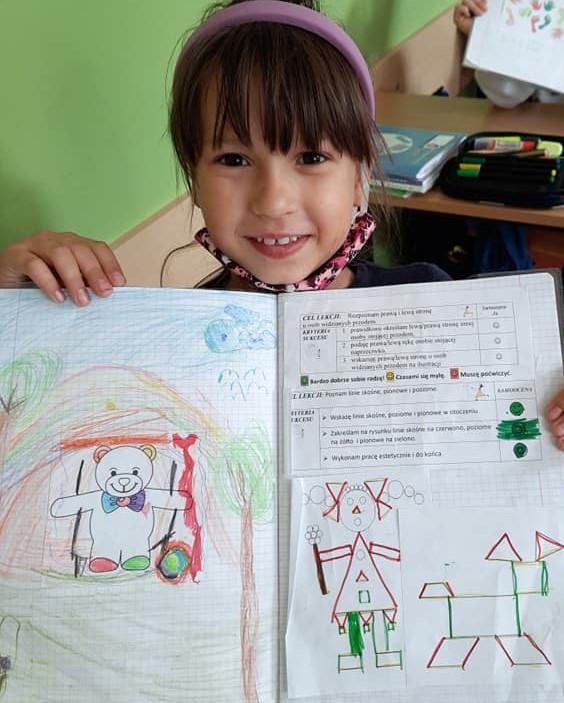 Fotografia przedstawia uczennicę klasy pierwszej trzymającą swój otwarty zeszyt.
