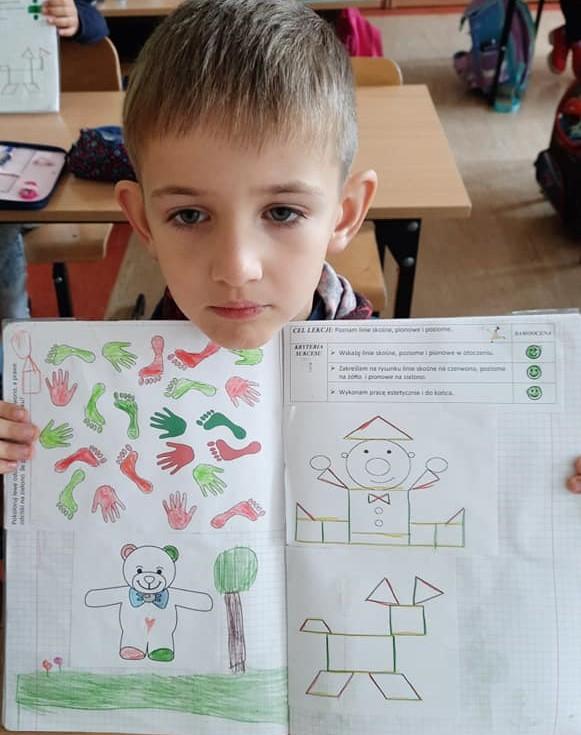 Fotografia przedstawia uczenia klasy pierwszej trzymającego swój otwarty zeszyt.