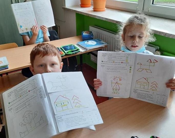 Fotografia przedstawia uczniów klasy pierwszej trzymających swoje otwarte zeszyty.
